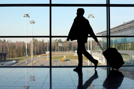 airport window: silhouette of man with luggage walking left near window in airport focus on street
