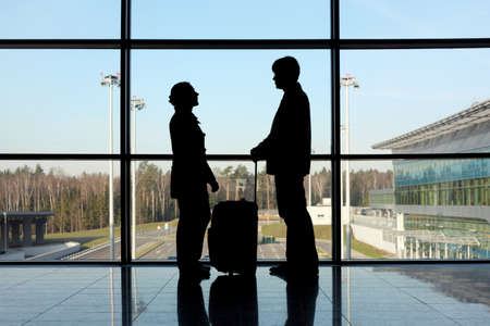 near side: silhouette of man and girl with luggage standing near window in airport side view Stock Photo
