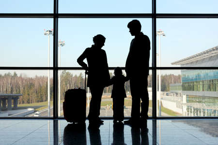silhouette of mother, father and daughter with luggage standing near window in airport  photo