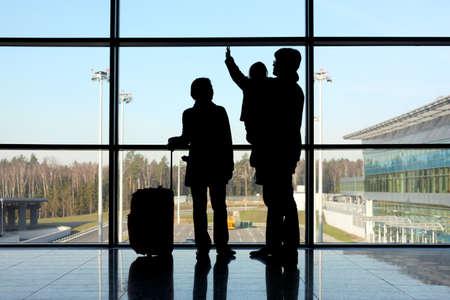 gente aeropuerto: silueta de la joven familia con el equipaje de pie cerca de una ventana en el aeropuerto