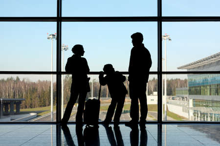 luggage airport: silhouette of mother, father and son with luggage standing near window in airport  Stock Photo