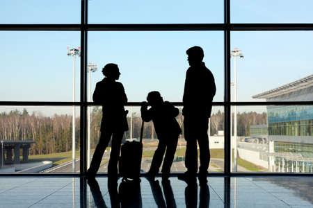 familia viaje: silueta de la madre, padre e hijo, con el equipaje de pie cerca de una ventana en el aeropuerto