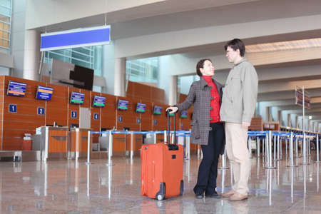 man and girl with red suitcase standing in airport hall Stock Photo - 11723076