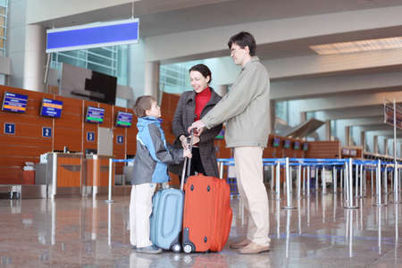 young family with boy standing in airport hall with suitcases side view photo