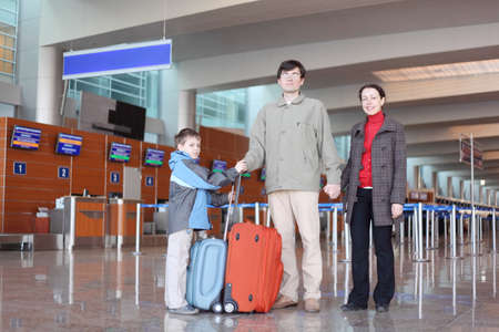 family with boy standing in airport hall with suitcases full body looking at camera photo