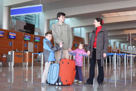 family with boy and girl standing in airport hall with two suitcases full body photo