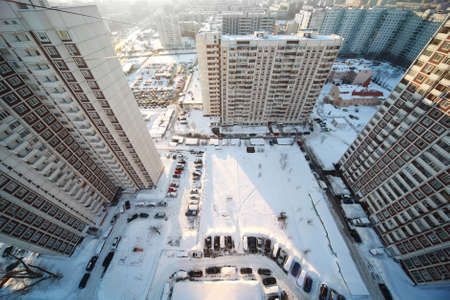 yard with three big dwelling houses, winter time, view from above photo