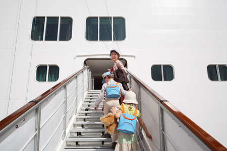ocean liner: little girl and boy with mother enter in large white passenger liner summer day