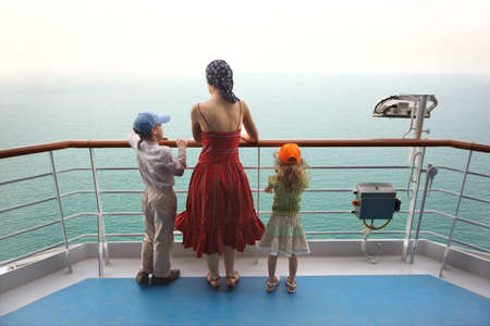 sandals: little boy and girl with mother standing on ship deck and looking at horizon Stock Photo