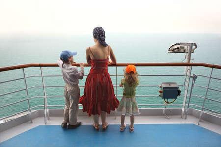 sandalias: niño y niña con la madre de pie en la cubierta del buque y mirando al horizonte Foto de archivo