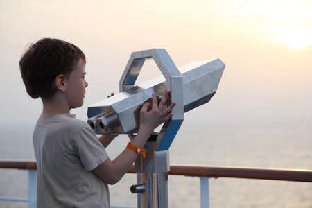 telescopes: little boy standing near binocular and looking into the distance side view half body