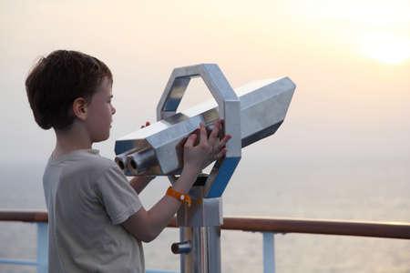 ni�o parado: ni�o de pie cerca de binoculares y mirar hacia el lado de la distancia ver el cuerpo de un medio Foto de archivo