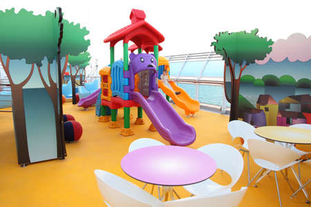 little boy slide on bright colorful childrens playground on cruise ship deck photo