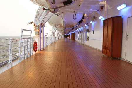 cruise ship deck with wooden brown floor and turned on lamps at side