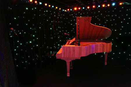 grand piano: grand piano at concert stage with black curtain decored multicolored lamps Stock Photo