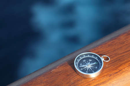 little cruise compass on wooden rail sea on background photo