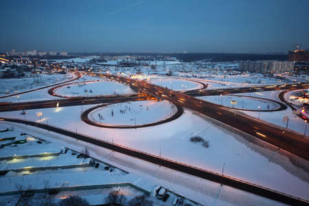 evening winter cityscape with big interchange, lighting columns and garages photo