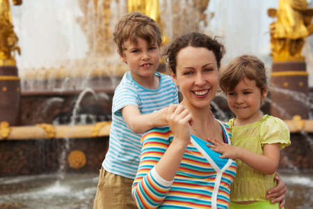 Portrait of family from three persons against fountain. Mum son and daughter have rest in park in afternoon. photo
