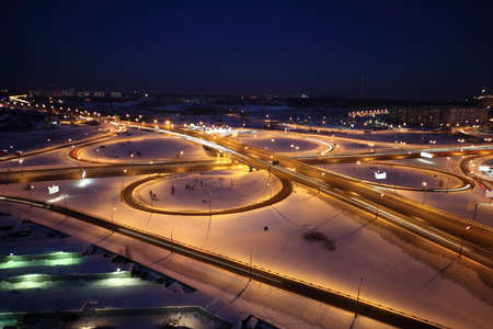 night winter cityscape with big interchange, lighting columns and garages, dark blue sky photo