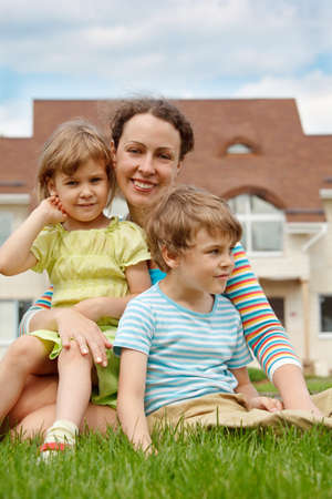Family of three people on lawn in front of house. Mother hugging her daughter and son. photo