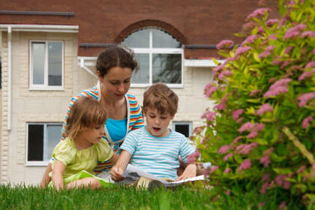 Family of three people on lawn in front of house. Mother with her daughter and son see paper. photo