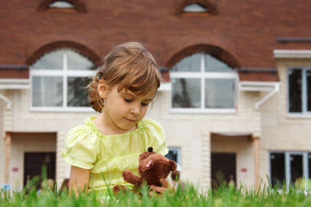 little girl sitting on lawn in front of new home. In her hands she holds toy teddy bear. photo