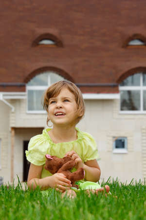 little girl sitting on lawn in front of new home. In her hands she holds toy wolf. vertical format photo