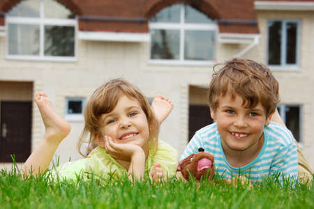 Smiling brother and sister lying on lawn in front of new home. In hands of boy toy. photo