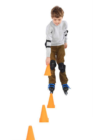 obstacle course: little boy with cone in hand rollerblading near orange cones looking down isolated on white Stock Photo