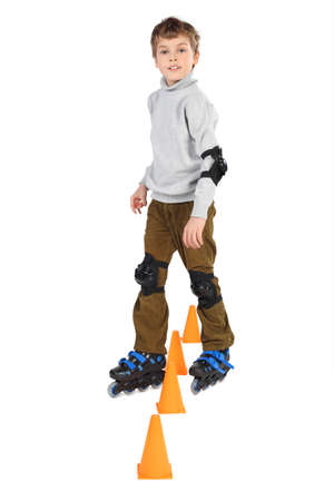 rollerblade: little roller blade boy clears orange cones obstacles looking at camera isolated on white