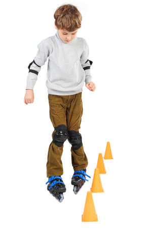 obstacle course: little boy rollerblading near orange cones looking down isolated on white Stock Photo