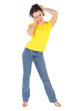 yellow shirt: young attractive woman in yellow shirt and jeans standing, hands behind head on white Stock Photo