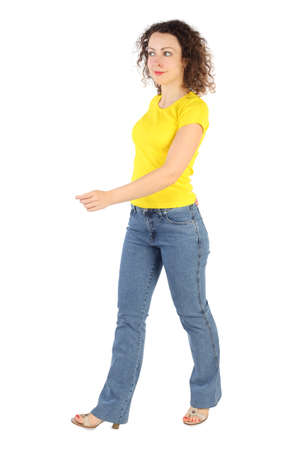 yellow shirt: tractive woman in yellow shirt and jeans walking left isolated on white Stock Photo