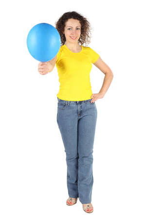 hands on hip: young attractive woman in yellow shirt and jeans offers blue balloon isolated on white Stock Photo