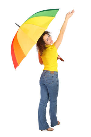 reached: young beauty woman in yellow shirt with multicolored umbrella standing with reached out a hand isolated on white, view from back Stock Photo