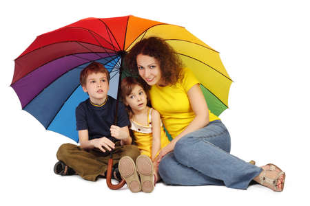 mother, daughter and son with big multicolored umbrella sitting isolated on white and looking at camera photo