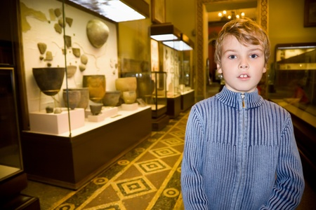 ancient relics: boy at excursion in historical museum near exhibits of ancient relics in glass cases Stock Photo