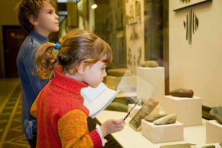 ancient relics: boy and little girl at excursion in historical museum near exhibits of ancient relics in glass cases