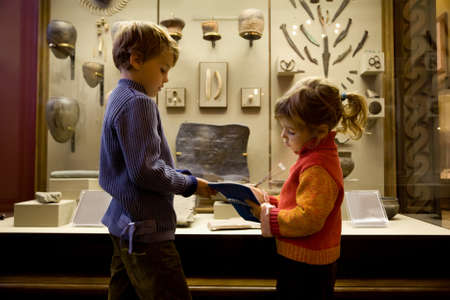 boy and little girl at excursion in historical museum near exhibits of ancient relics in glass cases, girl writes to writing-books