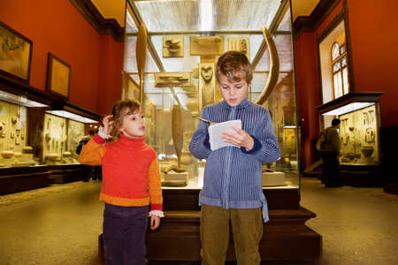 ancient relics: boy and little girl at excursion in historical museum near exhibits of ancient relics in glass cases, boy writes to writing-books