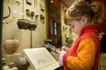 little girl writes to writing-books at excursion in historical museum near exhibits of ancient relics in glass cases