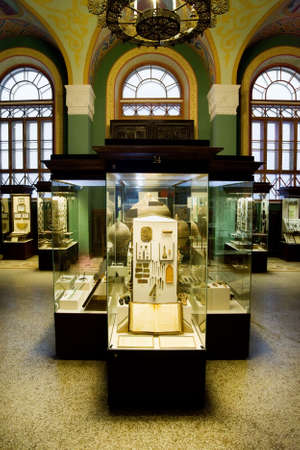 show cases: museum exhibits of ancient relics in glass cases against big windows Editorial
