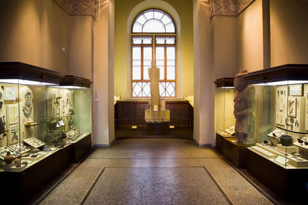 museum exhibits of ancient relics in glass cases, big window in centre