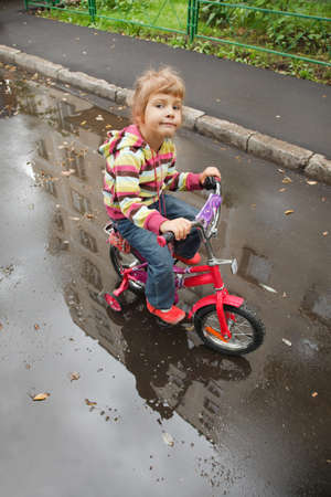 little girl goes on a bicycle on wet asphalt, reflexion in puddle photo