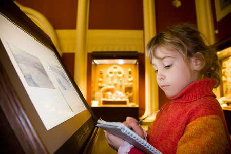 de pie niña cerca del monitor, escribe a la escritura-libros en excursión en el museo histórico contra exposiciones de antiguas reliquias en vitrinas