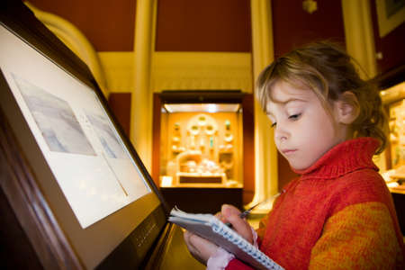 exhibit: little girl standing near monitor writes to writing-books at excursion in historical museum against exhibits of ancient relics in glass cases