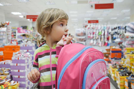 footgear: little girl in supermarket choose footwear with school bag in hands