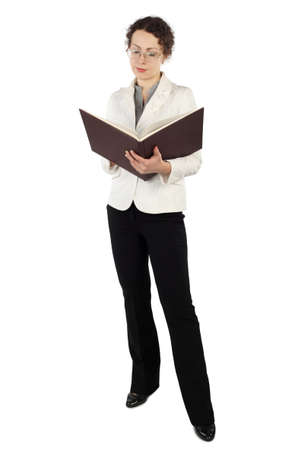 earnest: young attractive woman in business dress standing and reading big book isolated on white