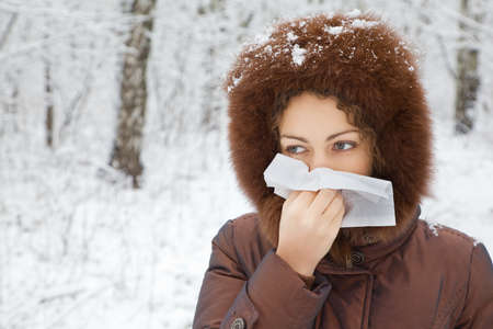 young woman with scarf blowing nose in wood in winter  photo