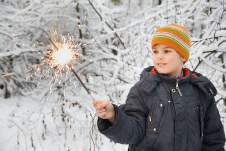 cheerful boy with Bengal fire in hand in winter in wood Stock Photo